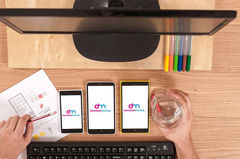 Window smartphones on table free PSD mockups