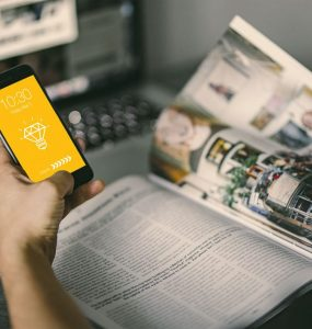 Man holding iPhone With magazine Mockup PSD