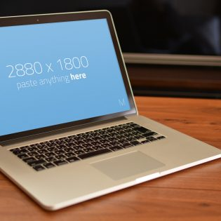 Macbook Pro on wooden table Mockup Free PSD